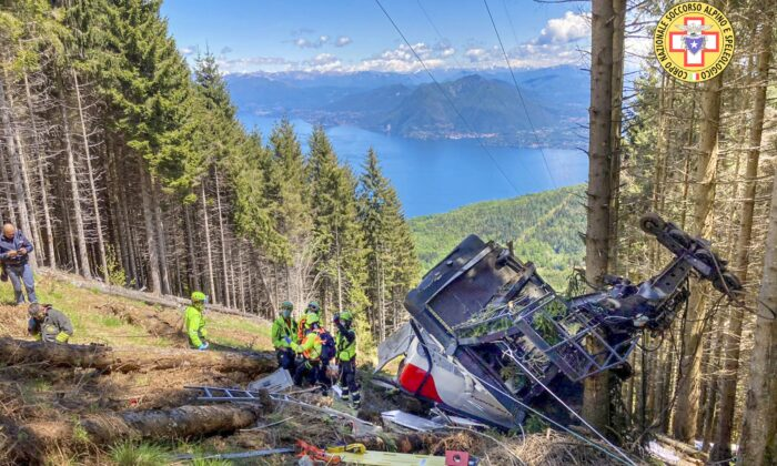 Rescuers work by the wreckage of a cable car after it collapsed near the summit of the Stresa-Mottarone line in the Piedmont region, northern Italy, on May 23, 2022. (Soccorso Alpino e Speleologico Piemontese via AP)