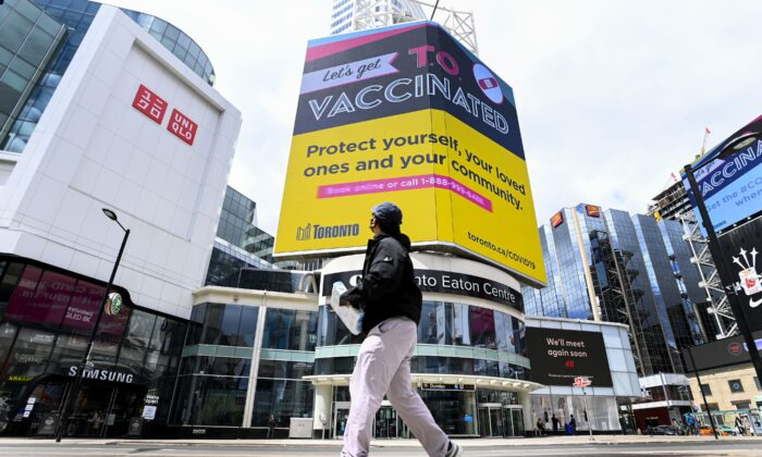 A man walks past an electronic COVID-19 vaccination sign at a deserted Dundas Square in Toronto on May 11, 2021. (The Canadian Press/Nathan Denette)