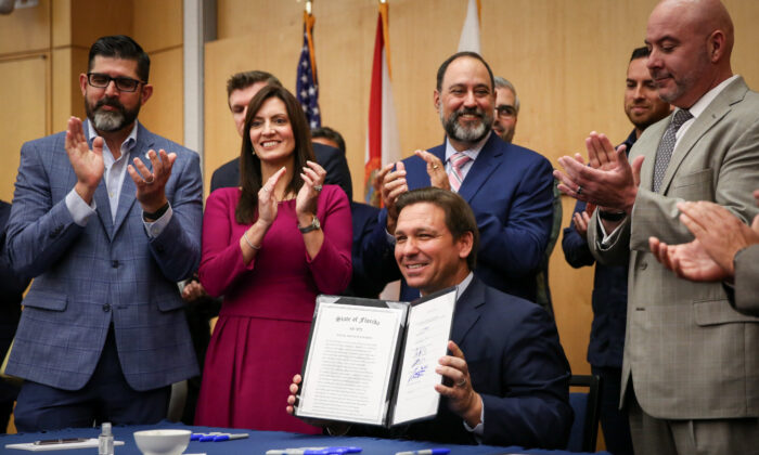 Florida Gov. Ron DeSantis signs into law Senate Bill 7072 at Florida International University in Miami on May 24, 2021. (Samira Bouaou/The Epoch Times)