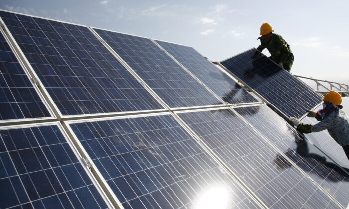 Workers install solar panels at a photovoltaic power station in Hami in northwestern China's Xinjiang Uyghur Autonomous Tegion on Aug. 22, 2011. (Chinatopix via AP)