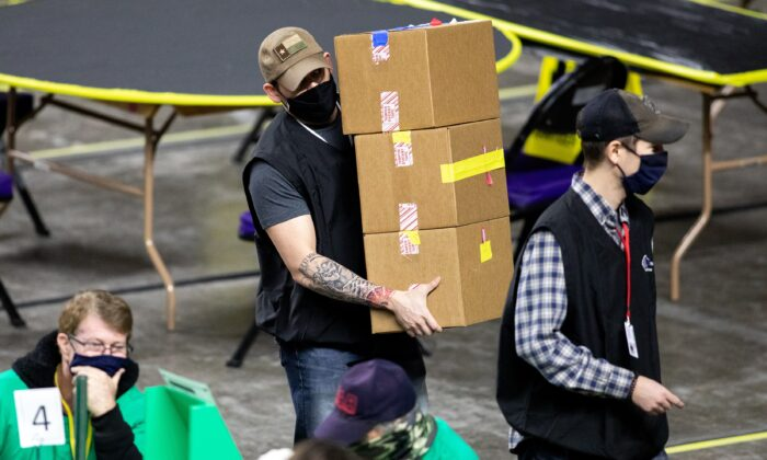 Contractors working for Cyber Ninjas, which was hired by the Arizona Senate, examine and recount ballots from the 2020 general election at Veterans Memorial Coliseum in Phoenix, Ariz., on May 1, 2021. (Courtney Pedroza/Getty Images)