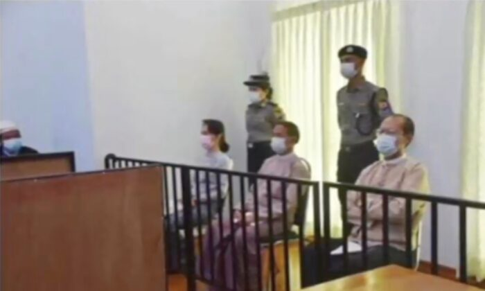 In this image from Myawaddy TV, a photograph shown during a news report showing the appearance of deposed Burma leader Aung San Suu Kyi, former President Win Myint, sitting 3rd from right, and former Naypyitaw Council chairman Dr. Myo Aung before a special court, shown while a report about Suu Kyi's case is read by a news presenter in Naypyitaw, Burma, on May 24, 2021. (Myawaddy TV via AP)