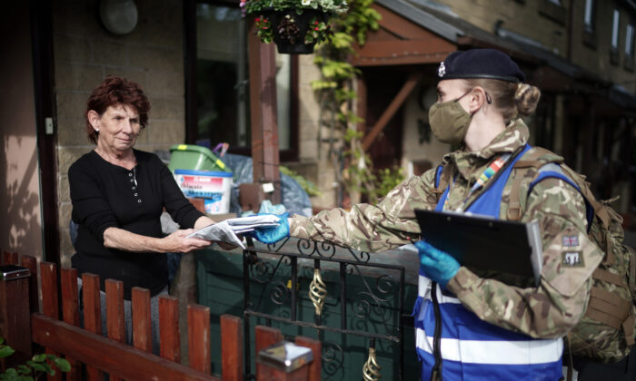 Gunners from the Royal Horse Artillery distribute COVID-19 polymerase chain reaction (PCR) tests to local residents in Bolton, England, on May 24, 2021. (Christopher Furlong/Getty Images)