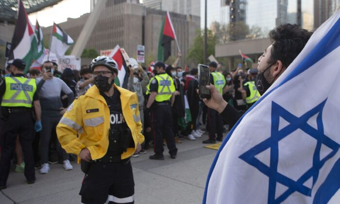 Police officers separate opposing Palestinian and Israeli supporters during a demonstration against the fighting in the Gaza Strip, in Toronto on May 15, 2021. (THE CANADIAN PRESS/Chris Young)