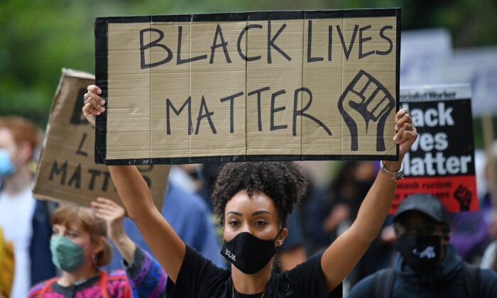 People hold up placards in support of the Black Lives Matter movement in a file photo (Justin Tallis/AFP via Getty Images)