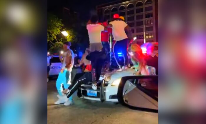 A crowd of party-goers in St. Louis, Missouri, are seen jumping and stomping on top of an officers patrol vehicle on May 23, 2021. (Courtesy of St. Louis Metropolitan Police Department)
