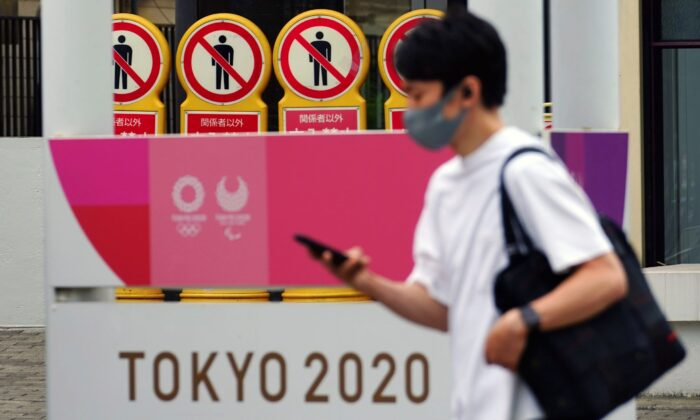 A man walks past a banner for the Tokyo 2020 Olympic and Paralympic Games in Tokyo, on May 11, 2021. (Eugene Hoshiko/AP Photo)