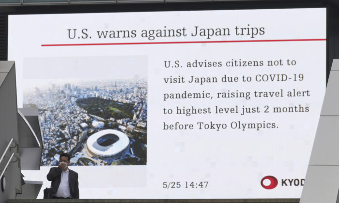 A man walks in front of a screen showing the news on U.S. warning against visits to Japan, in Tokyo on May 25, 2021. (Eugene Hoshiko/AP Photo)