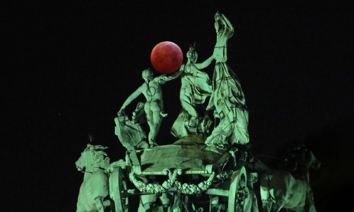 """The moon is seen beside a quadriga on the top of the Cinquantenaire arch during a total lunar eclipse, known as the """"Super Blood Wolf Moon,"""" in Brussels on Jan. 21, 2019. (Yves Herman/Reuters)"""