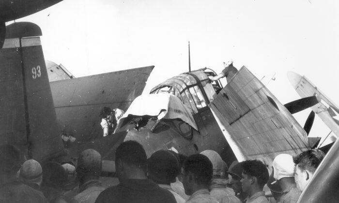 A deck crewman has covered up Loyce Deen while a decision is being made what to do with the aircraft, which sustained heavy battle damage. (Courtesy CDR Michael Cosgrove (Ret.), son of Robert D. Cosgrove via NavSource)