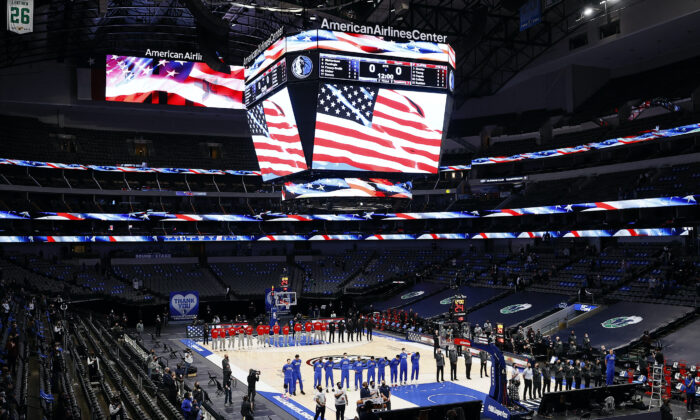 The Dallas Mavericks and the Atlanta Hawks stand for the National Anthem prior to tipoff of their NBA game at American Airlines Center in Dallas, Texas, on Feb. 10, 2021. (Tom Pennington/Getty Images)