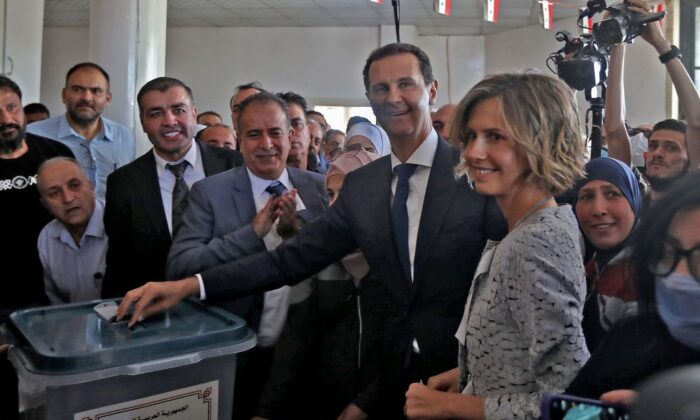 Syrian President Bashar al-Assad (C) and his wife Asma (R) cast their votes at a polling station in Douma, near Damascus, Syria, on May 26, 2021. (Louai Beshara/AFP via Getty Images)