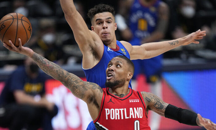 Portland Trail Blazers guard Damian Lillard (0) shoots next to Denver Nuggets forward Michael Porter Jr. (1) during the second half of Game 1 of a first-round NBA basketball playoff series in Denver, Colo., on May 22, 2021. (Jack Dempsey/AP Photo)