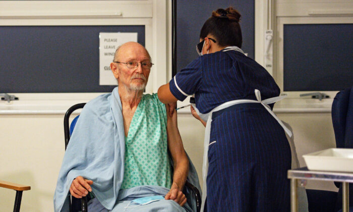 """A nurse adminsters the Pfizer-BioNtech COVID-19 vaccine to patient William """"Bill"""" Shakespeare (L), 81, at University Hospital in Coventry, England, on Dec. 8, 2020. (Jacob King/POOL/AFP via Getty Images)"""