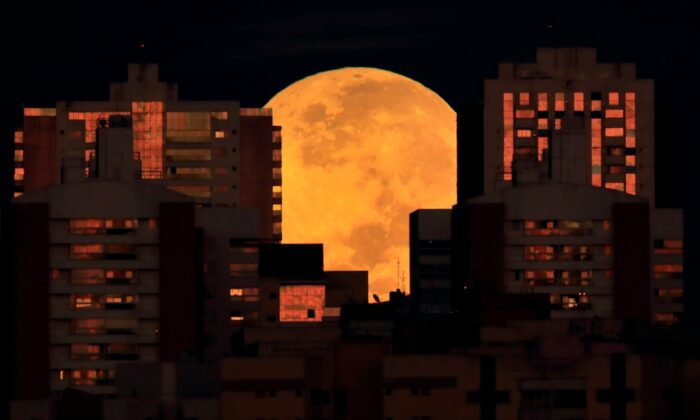 The moon is partially covered by buildings in Brasilia, Brazil, at the start of a total lunar eclipse early on May 26, 2021. (Eraldo Peres/AP Photo)