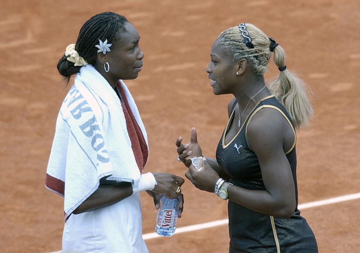 Serena Williams (R) talks with her sister Venus