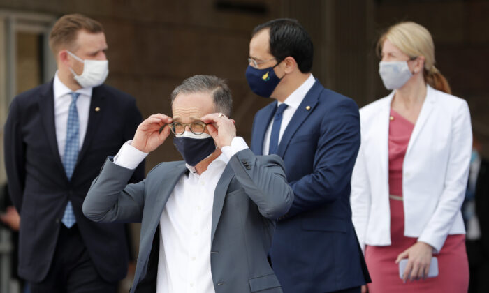 German Foreign Minister Heiko Maas (second left) adjusts his glasses prior to a group photo of EU foreign ministers in Lisbon on May 27, 2021. (Armando Franca/AP Photo)