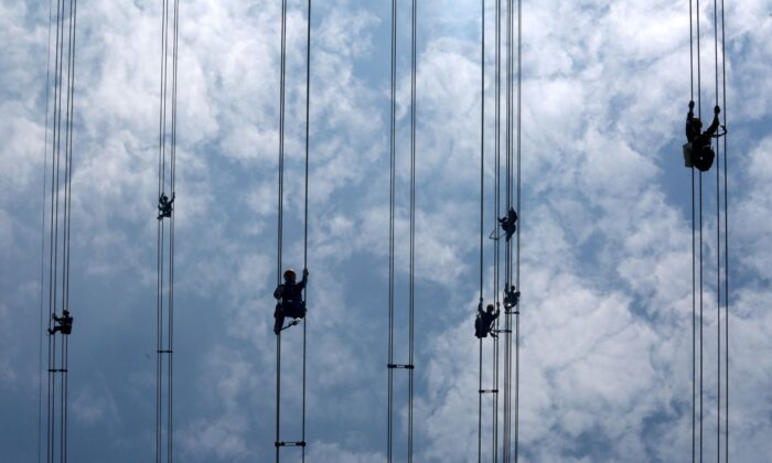 Workers of grid operator China Southern Power Grid inspect power cables connecting transmission towers in Dongguan, Guangdong province, China, on May 29, 2018.(Stringer/Reuters)