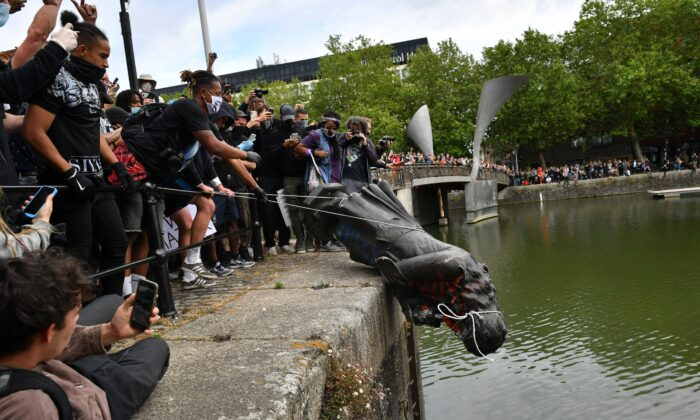 Protesters throwing the statue of Edward Colston into Bristol harbour during a Black Lives Matter protest rally, UK, on Jane 7, 2020. (PA Wire/PA Images)