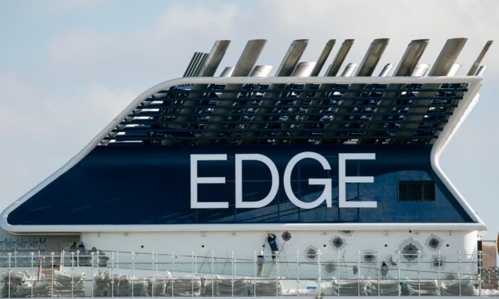 """Workers are pictured on the deck of the French-made cruise ship """"Celebrity Edge"""" of the US company of tourism cruise, Celebrity Cruise, as it leaves the shipyards of Saint-Nazaire to go to Miami, United States in Saint-Nazaire, western France on Nov. 4, 2018. (Sebastien Salom Gomis/AFP via Getty Images)"""
