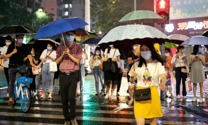 People wearing protective face mask walk under their umbrellas as it rains in Shenzhen in China's southern Guangdong province on May 22, 2020. (Photo by NOEL CELIS/AFP via Getty Images)