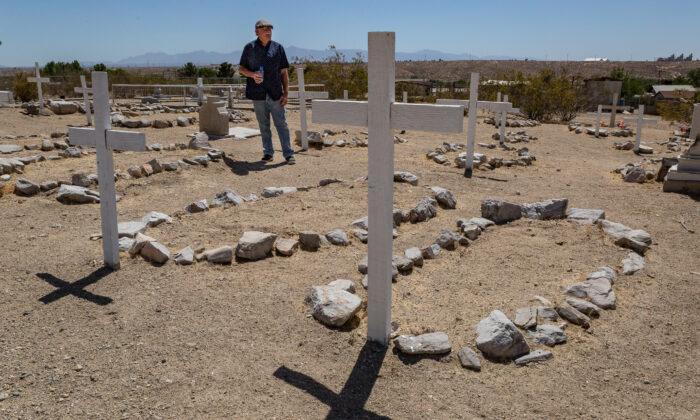 Honorary Mayor Joe Manners walks through the cemetery in Oro Grande, Calif., on May 18, 2021. (John Fredricks/The Epoch Times)