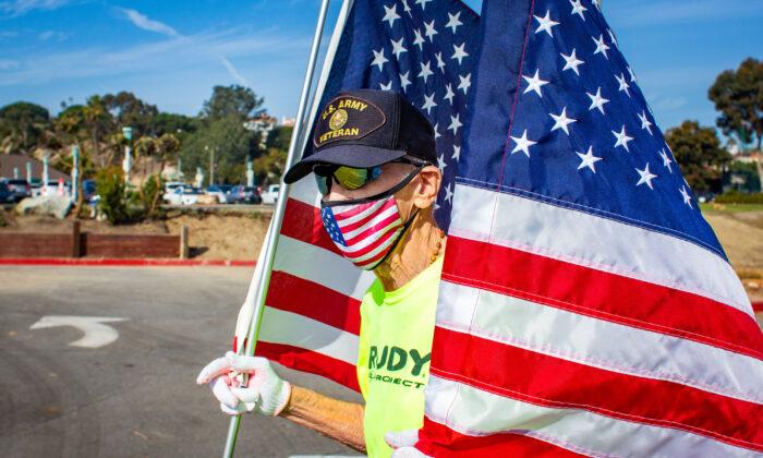 89-year-old runner Robert Kohler runs the virtual 2020 Dana Point Turkey Trot holding two large American Flags in Dana Point, Calif., on Nov. 21, 2020. (John Fredricks/The Epoch Times)