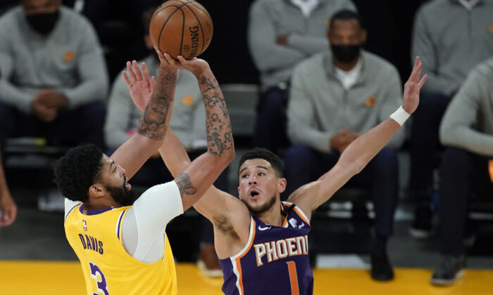 Los Angeles Lakers forward Anthony Davis (3) shoots over Phoenix Suns guard Devin Booker (1) during the first half in Game 3 of an NBA basketball first-round playoff series in Los Angeles, Calif., on May 27, 2021. (Marcio Jose Sanchez/AP Photo)