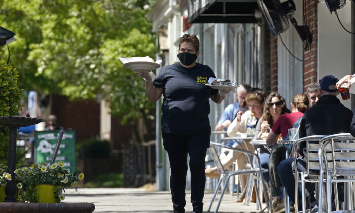A member of the wait staff delivers food to outdoor diners along the sidewalk at the Mediterranean Deli restaurant in Chapel Hill, N.C., on April 16, 2021. (Gerry Broome/AP Photo)