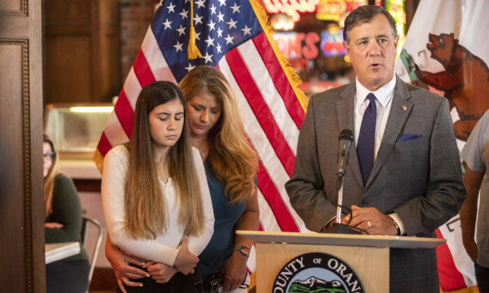 Alexis Cloonan, left, Aiden Leos' sister, and Carole Ybanez, a family friend, stand behind Orange County Supervisor Don Wagner at a news conference on May 27, 2021 on the freeway shooting that left 6-year-old Aiden dead. (Allen J. Schaben/Los Angeles Times/TNS)