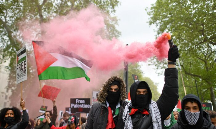 Pro-Palestine demonstrators hold placards as they gather to march in central London on May 22, 2021. (Justin Tallis/AFP via Getty Images)