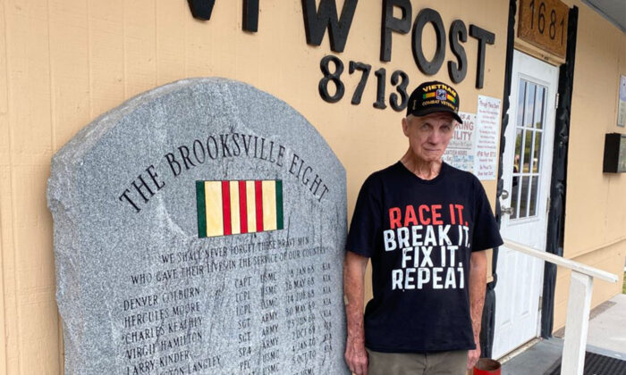 Ron McCombs, retired United States Army, stands at attention beside The Brooksville Eight monument at VFW Post 8713 in Brooksville, Florida. (Patricia Tolson/The Epoch Times)
