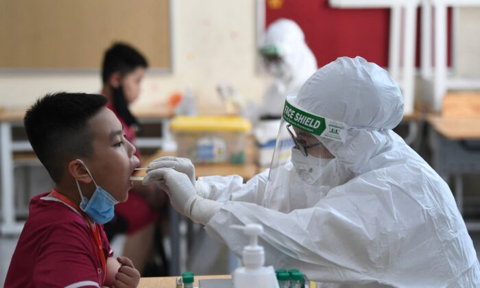 A health worker wearing personal protective equipment (PPE) conducts a COVID-19 swab test on a student at the Vinschool private school in Hanoi, Vietnam, on May 22, 2021. (Nhac Nguyen/AFP via Getty Images)