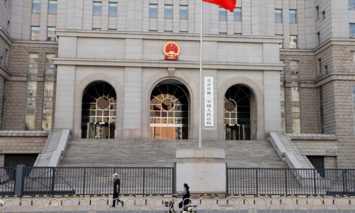 People walk past one of the entrances of Beijing No. 2 Intermediate People's Court where Australian writer Yang Hengjun is expected to face trial on espionage charges, in Beijing, China, on May 27, 2021. (Carlos Garcia Rawlins/Reuters, File Photo)