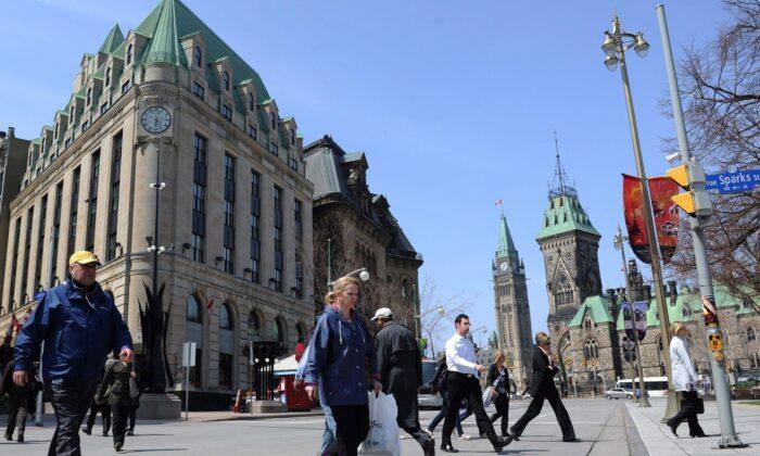 Pedestrians cross Elgin Street in view of Parliament Hill in Ottawa in a file photo. (The Canadian Press/Sean Kilpatrick)