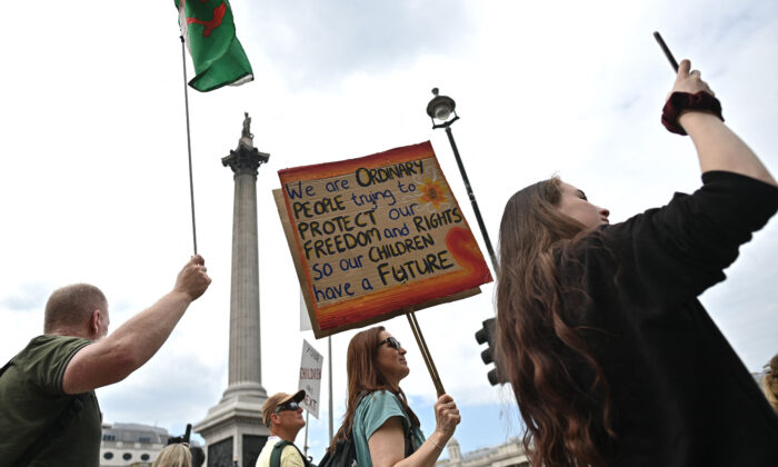 Protesters carry placards during a 'Unite For Freedom' rally against CCP virus vaccine passport and government lockdown restrictions, in Trafalgar Square, central London on May 29, 2021. (Ben Stansall/AFP via Getty Images)