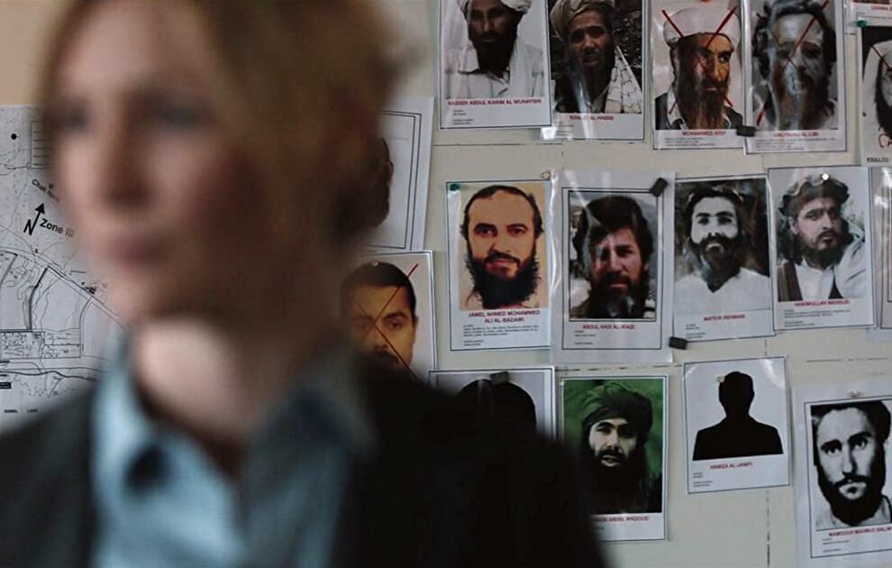 woman standing next to suspect photos in Zero Dark Thirty