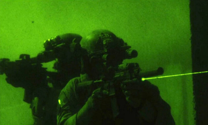 """Members of US Navy SEAL Team Six using night vision devices and laser sights in the hunt for Osama bin Laden, in """"Zero Dark Thirty."""" (Jonathan Olley/Columbia Pictures)"""
