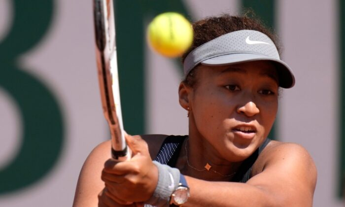 Japan's Naomi Osaka returns the ball to Romania's Patricia Maria Tig during their first round match of the French Open tennis tournament at the Roland Garros stadium, in Paris, France, on May 30, 2021. (Christophe Ena/AP Photo)
