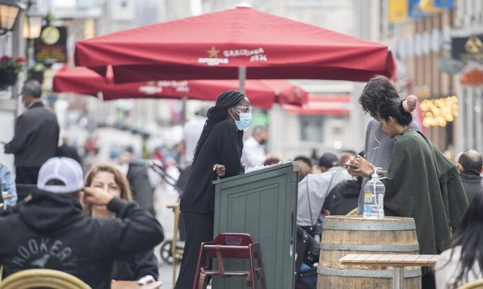 A greeter wears a face mask as people wait for a table at a restaurant in Old Montreal, on May 30, 2021, as the COVID-19 pandemic continues in Canada and around the world. (The Canadian Press/Graham Hughes