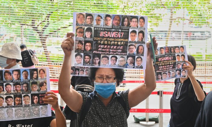 A woman holds up a paper with the words #Save47 outside of the West Kowloon court building in Hong Kong on May 31, 2021. (Sung Pi-lung/The Epoch Times)