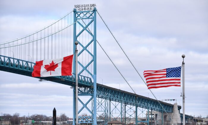 Canadian and American flags fly near Ambassador Bridge at the Canada-U.S. border crossing in Windsor, Ont., on March 21, 2020, when the border was closed to non-essential travel. (The Canadian Press/Rob Gurdebeke)