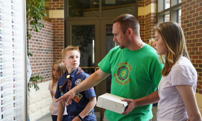 Drew Barczak tells his children about the fallen soldiers on a Wall of Honor displayed at Oswego Township Hall in Oswego, Illinois on May 31, 2021. (Cara Ding/The Epoch Times)