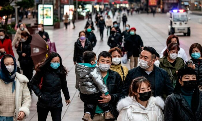 People wearing protective face masks walk along a street in Shanghai, China on Feb. 21, 2020. (NOEL CELIS/AFP via Getty Images)