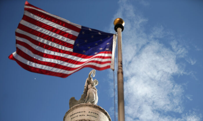 A U.S. flag with 15 stripes and 15 stars, like the one that was flown Fort McHenry during the War of 1812, frames the Battle Monument in Baltimore, Maryland, on Sept. 12, 2014. (Chip Somodevilla/Getty Images)