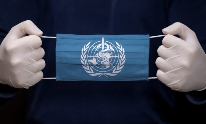 A doctor holds a medical face mask with the World Health Organization's (WHO) flag. (kcube-Baytur/Shutterstock)