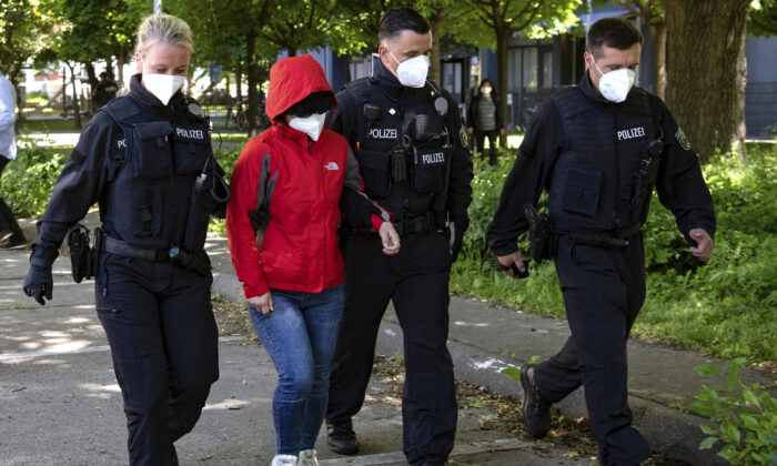 Police officers lead a woman to a vehicle during a raid against a group of people suspect to brought Vietnamese people to Europe on fraudulently obtained visas, in Berlin, on May 31, 2021. (Paul Zinken/dpa via AP)
