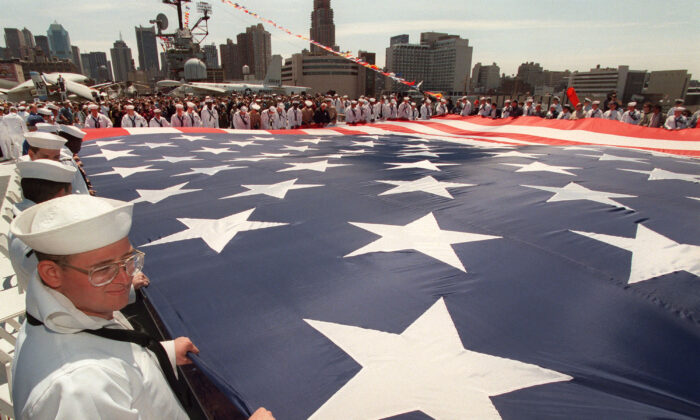 A U.S. war veterans and active duty personnel join others in rolling up a fifty by ninety-foot U.S. flag on the deck of the Intrepid Sea Air Space Museum in New York, during a Memorial Day ceremony, on May 26, 1997. (Stan Honda/AFP via Getty Images)