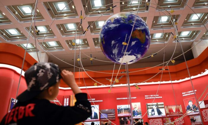 A boy looks at the BeiDou Navigation Satellite System at an exhibition marking the 40th anniversary of China's reform and opening up at the National Museum of China in Beijing on Feb. 27, 2019. (WANG ZHAO/AFP via Getty Images)