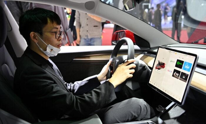 A man is seen inside of a Tesla car during the 19th Shanghai International Automobile Industry Exhibition in Shanghai on April 19, 2021. (Hector Retamal/AFP via Getty Images)